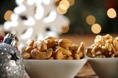 Walnusskern-Acajounüsse und pistachions in einer Schüssel auf dem Brett mit unscharfem christimas Hintergrund Stockbilder