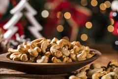 Walnusskern-Acajounüsse und pistachions in einer Schüssel auf dem Brett mit unscharfem christimas Hintergrund Stockfotografie