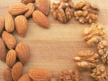 Walnut and almond frame on wooden background Stock Photos