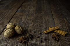 Walnut anise cinnamon sticks and pepper on a wooden background Royalty Free Stock Images