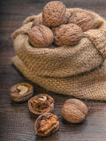 Walnut on a bag. Pile of walnuts in shellin a bag on a wooden background . Linen sack with walnuts in the background. toning Royalty Free Stock Image