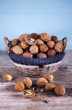 Walnut basket full of whole nuts in shells and some broken. Sunny on wooden table Stock Photo