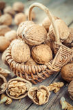 Walnut in basket on old wooden table Royalty Free Stock Image
