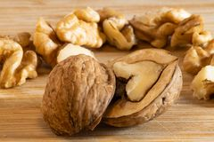 Cracked walnut in-front of other walnuts stock images