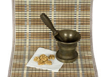 Walnut and the copper pounder (mortar) on the matting Stock Image