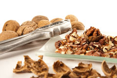 Walnut and a cracked walnut with nutcracker Royalty Free Stock Photo