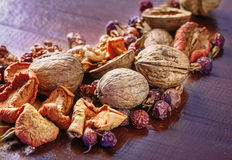 Walnut, dried fruit and dry rose hips on a wooden board Royalty Free Stock Photos
