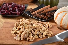 Walnut halves on a cutting board. With cranberries, cinnamon, star anise and other holiday food ingredients stock images