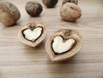 Walnut hearts. Two walnut hearts on wooden background Royalty Free Stock Images