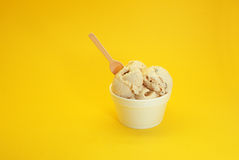 Walnut ice cream. Served in white cups with a spoon and a yellow background Stock Photo