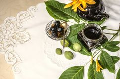 Walnut jam with a black teapot with orange lilies lying on an embroidered tablecloth. Walnut jam in a glass jar with a black porcelain teapot with orange lilies Royalty Free Stock Photo