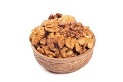 Walnut kernels in brown cup. Isolated on the white background Royalty Free Stock Photo