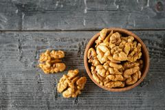 Walnut kernels and a clay bowl with peeled walnuts on a rustic table. The view from the top. Walnut kernels and a clay bowl with peeled walnuts on a rustic table royalty free stock photography