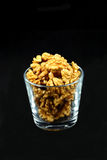 Walnut kernels in a cup on black Royalty Free Stock Images