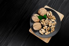 Walnut and walnut kernels on the plate on rustic wooden black background. Stock Image