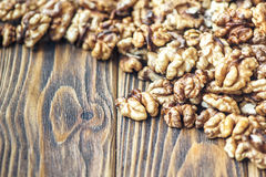 Walnut kernels on rustic old wooden table. Chopped walnuts. Close-up Royalty Free Stock Photo