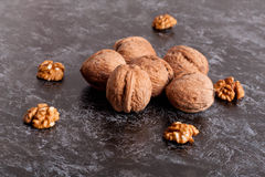 Walnut kernels and whole walnuts on black table Stock Photos