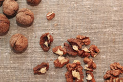 Walnut kernels and whole walnuts. On burlap Royalty Free Stock Photos