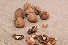 Walnut kernels and whole walnuts. On burlap Stock Photo