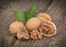 Walnut kernels and whole walnuts on rustic old wooden table Royalty Free Stock Images