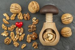 Walnut kernels and whole walnuts on slate.  Walnuts and wooden nutcracker. We like walnuts. Stock Photo