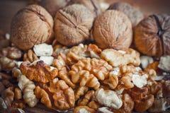 Walnut kernels and whole walnuts wood background Stock Photography