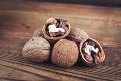 Walnut kernels and whole walnuts wood background Stock Image