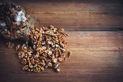 Walnut kernels and whole walnuts wood background Royalty Free Stock Images