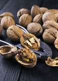 Walnut kernels and whole walnuts on wooden background.  Royalty Free Stock Photos