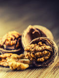 Walnut kernels and whole walnuts on wooden board. Royalty Free Stock Photos