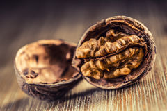 Walnut kernels and whole walnuts on wooden board. Royalty Free Stock Images