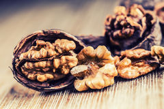 Walnut kernels and whole walnuts on wooden board. Royalty Free Stock Image