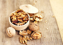 Walnut kernels in a wooden bowl and whole walnuts Royalty Free Stock Photos