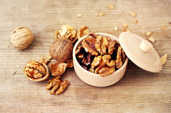 Walnut kernels in a wooden bowl and whole walnuts Stock Photos