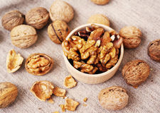 Walnut kernels in a wooden bowl and whole walnuts Stock Photography