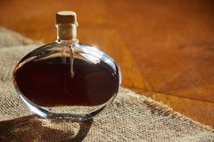 Walnut liquor in bottle on a wooden table. Homemade alcohol drink Stock Images