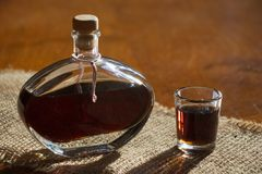 Walnut liquor in bottle on a wooden table. Homemade alcohol drink Royalty Free Stock Image
