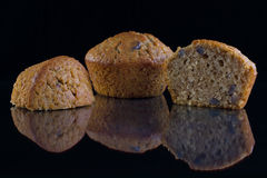 Walnut Muffins. Fresh baked walnut muffins on a reflective black surface Royalty Free Stock Photos