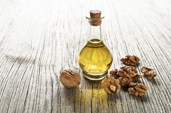 Walnut oil. In a glass bottle on a wooden background royalty free stock photo
