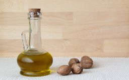 Walnut oil in glass carafe. Glass carafe of walnut oil and walnuts on wooden background Royalty Free Stock Photos