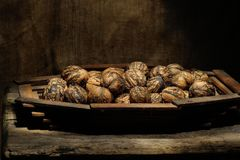 Walnut in a peel on  wooden platter Royalty Free Stock Image