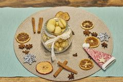 Walnut shaped butter cookies in glass vase decorated with white ribbon with bow, cinnamon sticks, slices of dried orange stock images
