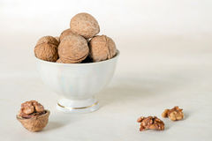 Walnut in a shell are stacked in a white cup. Next peeled nuts. Vegetable protein is an analogue of animal. Light background royalty free stock images