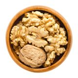 Walnut and shelled walnut kernel halves in wooden bowl stock photo