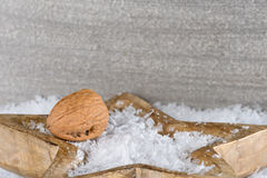 Walnut on a snowy wooden star Royalty Free Stock Images