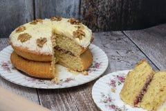 Walnut sponge cake on wooden background. Close up stock image