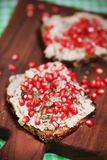 Walnut spread on wholegrain bread with pomegranate seeds Stock Images