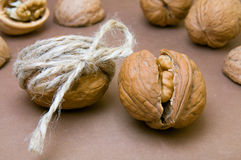 Walnut tied with twine and cracked walnut on the background of o Royalty Free Stock Photos
