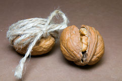 Walnut tied with twine and cracked walnuts on a brown background Royalty Free Stock Photos