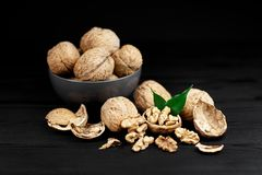 Walnut and walnut kernels on the plate on rustic wooden black background. Royalty Free Stock Image